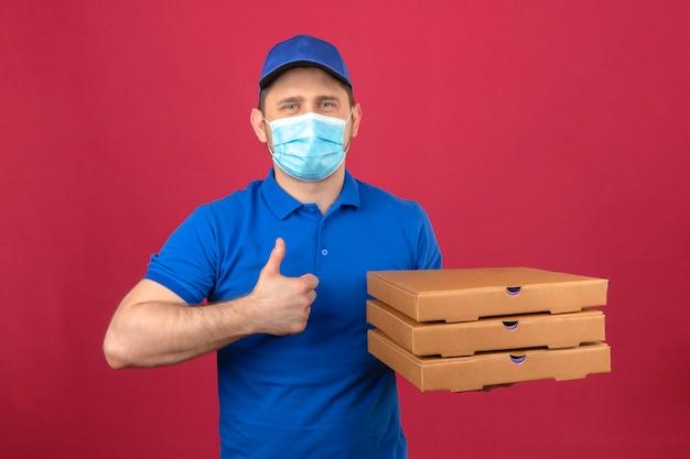 Jovem entregador de camisa pólo azul e boné com máscara médica, segurando uma pilha de caixas de pizza, mostrando o polegar para cima com uma cara feliz sobre um fundo rosa isolado