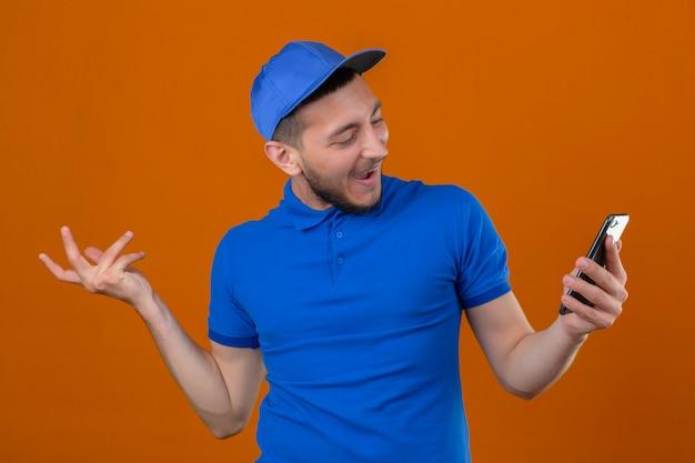 Jovem entregador de camisa pólo azul e boné olhando para o celular na mão com uma cara feliz sorrindo alegremente sobre um fundo laranja isolado