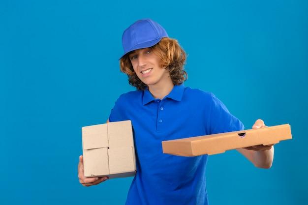 Jovem entregador de camisa pólo azul e boné segurando uma caixa de papelão esticando uma caixa de pizza, sorrindo amigável em pé sobre um fundo azul isolado