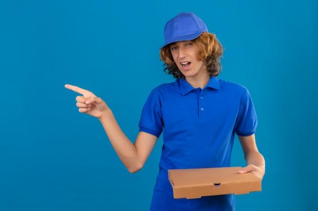 Jovem entregador de camisa pólo azul e boné segurando uma caixa de pizza apontando para o lado e parecendo insatisfeito com o fundo azul isolado
