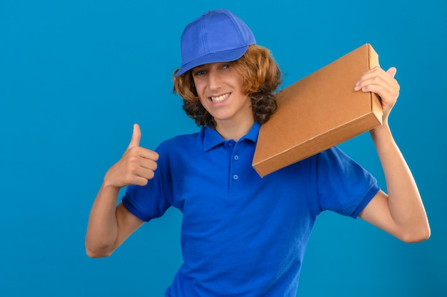 Jovem entregador de camisa pólo azul e boné segurando uma caixa de pizza no ombro e mostrando o polegar sorrindo alegremente em pé sobre um fundo azul isolado