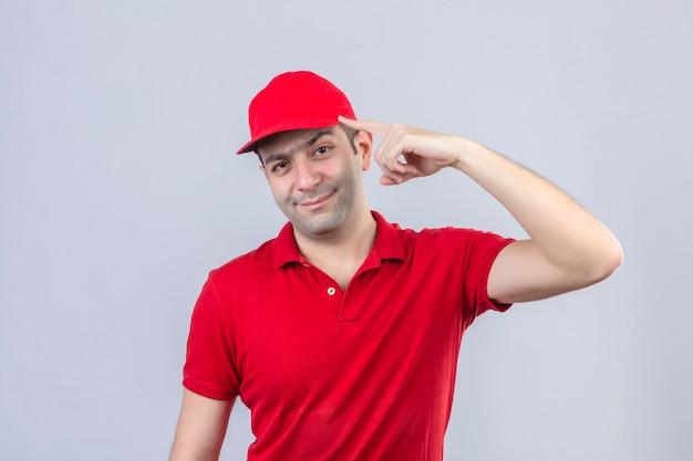 Jovem entregador de camisa pólo vermelha e boné apontando para o templo, com o dedo pensando em uma tarefa sobre um fundo branco