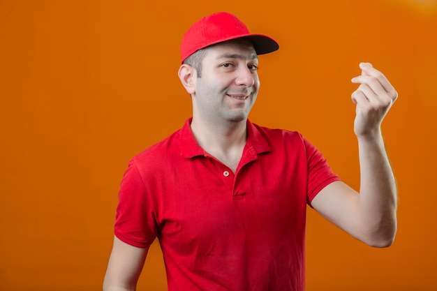 Jovem entregador de camisa polo vermelha e boné com sorriso no rosto, fazendo dinheiro gesto com a mão na parede laranja isolada