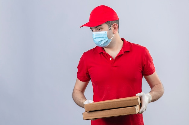 Jovem entregador de camisa polo vermelha e boné em máscara médica segurando caixas de pizza, olhando para o lado com cara séria sobre parede branca isolada