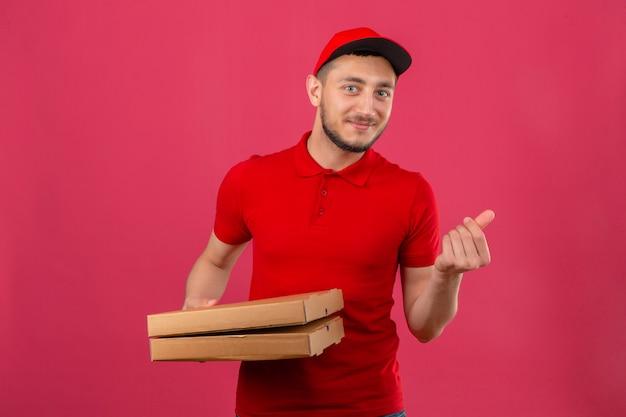 Jovem entregador de camisa pólo vermelha e boné em pé com caixas de pizza preocupado com dinheiro fazendo um gesto de dinheiro com a mão sorrindo sobre fundo rosa isolado
