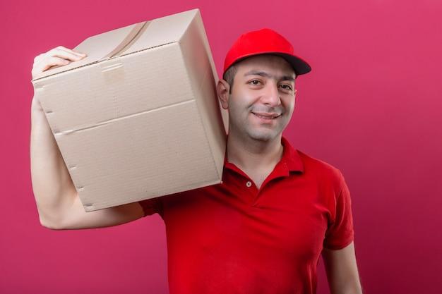 Jovem entregador de camisa pólo vermelha e boné em pé com uma caixa de papelão no ombro, sorrindo confiante sobre um fundo rosa isolado