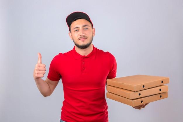 Jovem entregador de camisa pólo vermelha e boné em pé com uma pilha de caixas de pizza, parecendo confiante mostrando o polegar para cima sobre um fundo isolado