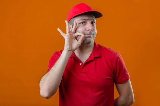 Jovem entregador de camisa pólo vermelha e boné fazendo gesto de silêncio, como fechar a boca com um zíper sobre fundo laranja isolado