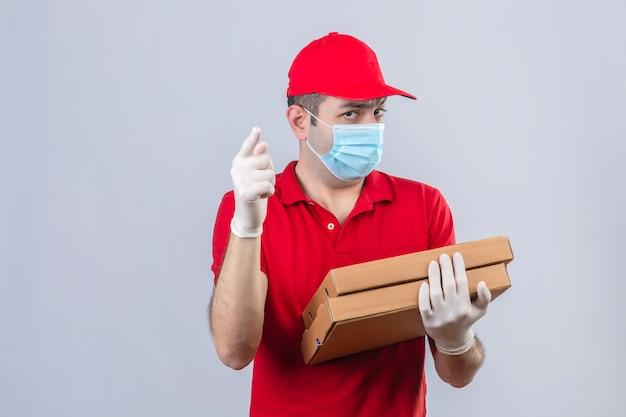 Jovem entregador de camisa polo vermelha e boné na máscara médica segurando caixas de pizza, olhando com reprovação para a câmera e apontando o dedo para você sobre parede branca isolada