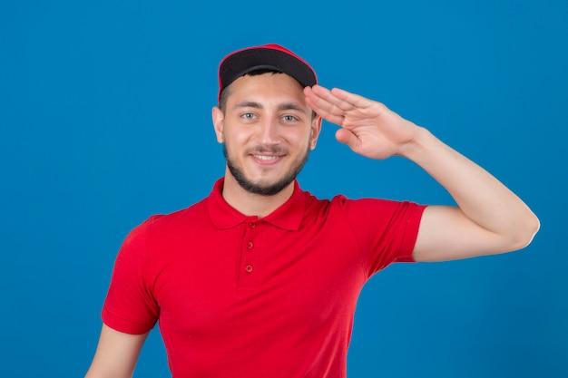 Jovem entregador de camisa pólo vermelha e boné saudando parecendo confiante sobre um fundo azul isolado