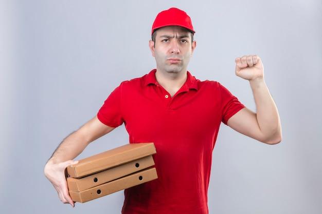 Jovem entregador de camisa polo vermelha e boné segurando caixas de pizza, franzindo a testa levantando o punho com expressão negativa no rosto sobre parede branca isolada
