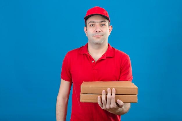 Jovem entregador de camisa polo vermelha e boné segurando caixas de pizza, sorrindo em pé amigável sobre parede azul isolada