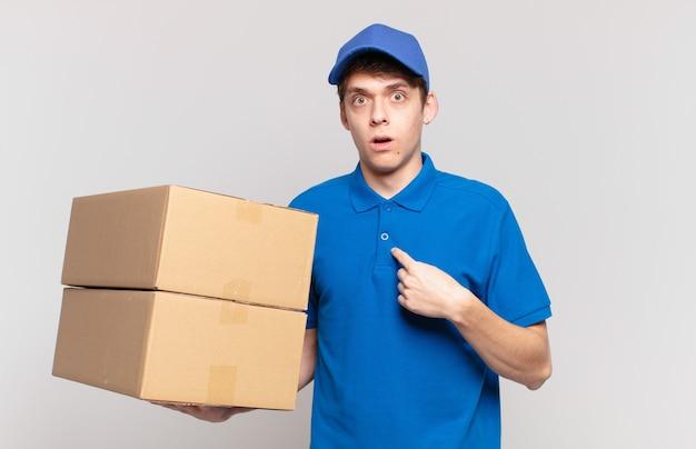 Jovem entregador de pacotes parecendo chocado e surpreso com a boca aberta, apontando para si mesmo