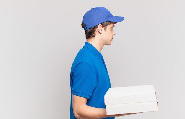 Jovem entregador de pizza em vista de perfil olhando para copiar o espaço à frente, pensando, imaginando ou sonhando acordado