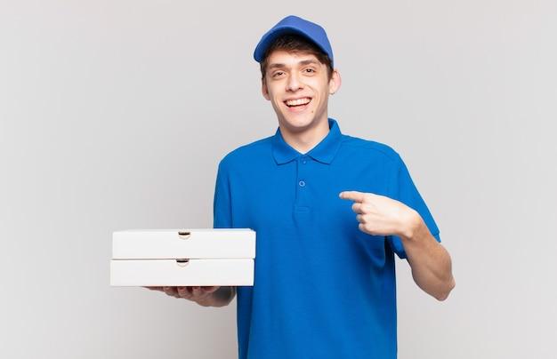 Jovem entregador de pizza se sentindo feliz, surpreso e orgulhoso, apontando para si mesmo com um olhar animado e surpreso