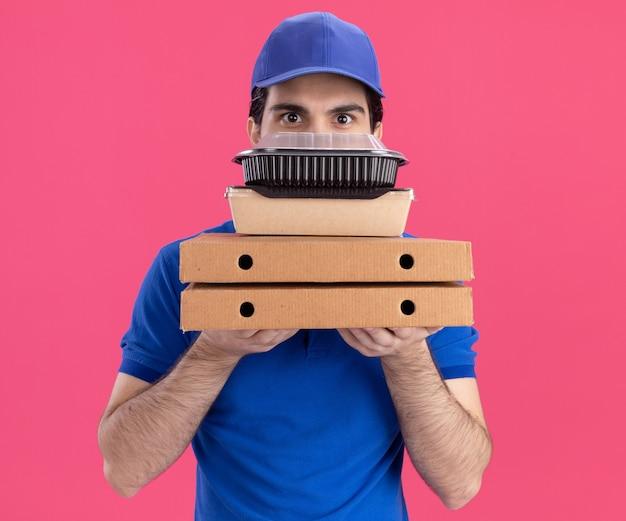 Jovem entregador de uniforme azul e boné impressionado segurando pacotes de pizza com um recipiente de comida e um pacote de papel para comida olhando para frente por trás deles, isolado na parede rosa