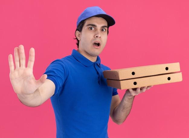 Jovem entregador de uniforme azul e boné, impressionado, segurando pacotes de pizza olhando para a frente, fazendo gesto de pare isolado na parede rosa