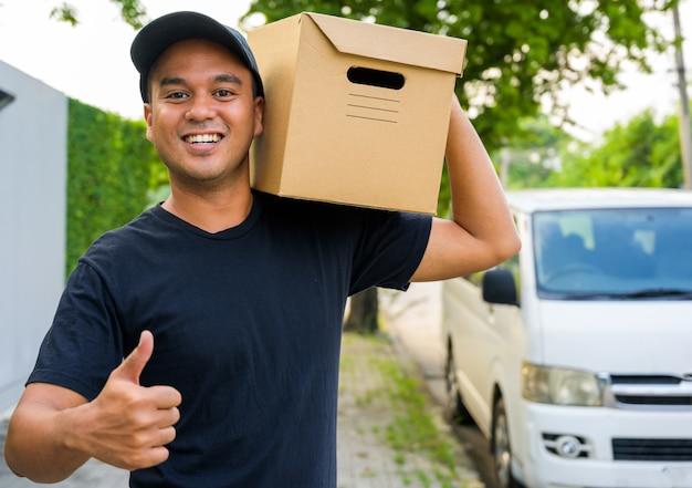 Jovem entregador de uniforme preto mostra thumbup e segurando uma caixa de papel.