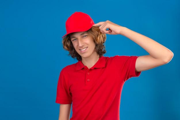 Jovem entregador de uniforme vermelho apontando para o templo com o dedo pensando em uma tarefa sobre um fundo azul isolado