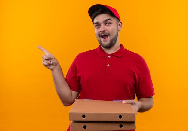 Jovem entregador de uniforme vermelho e boné apontando com o dedo para o lado segurando caixas de pizza com um sorriso largo