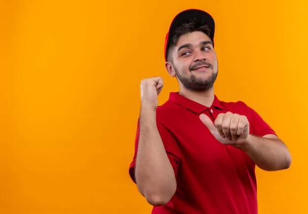Jovem entregador de uniforme vermelho e boné apontando para trás, sorrindo confiante