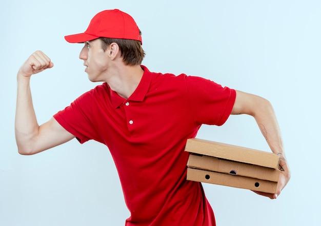 Jovem entregador de uniforme vermelho e boné correndo para entregar caixas de pizza para um cliente na parede branca