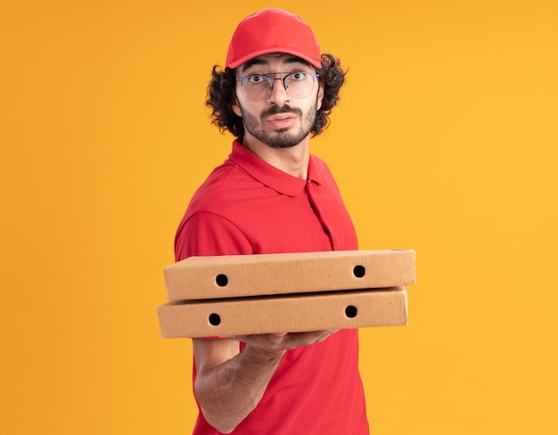 Jovem entregador de uniforme vermelho e boné impressionado, de óculos, em vista de perfil, estendendo os pacotes de pizza para a frente, olhando para a frente, isolado na parede laranja