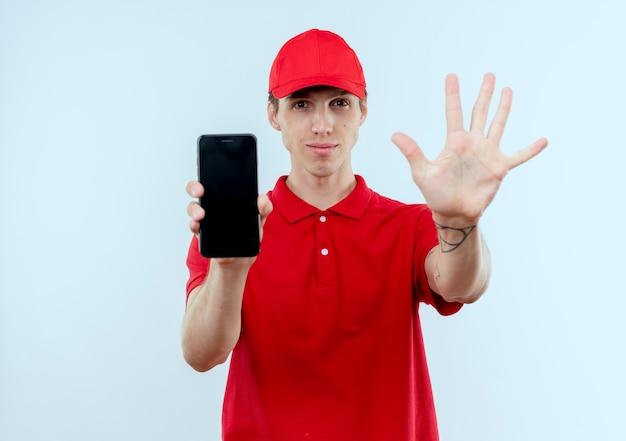 Jovem entregador de uniforme vermelho e boné mostrando smartphone aparecendo e apontando para cima com os dedos número cinco sorrindo em pé sobre uma parede branca