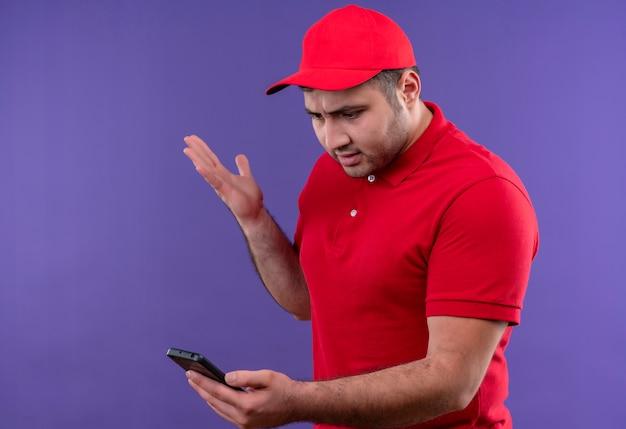 Jovem entregador de uniforme vermelho e boné olhando para a tela do smartphone descontente e desapontado em pé sobre o roxo