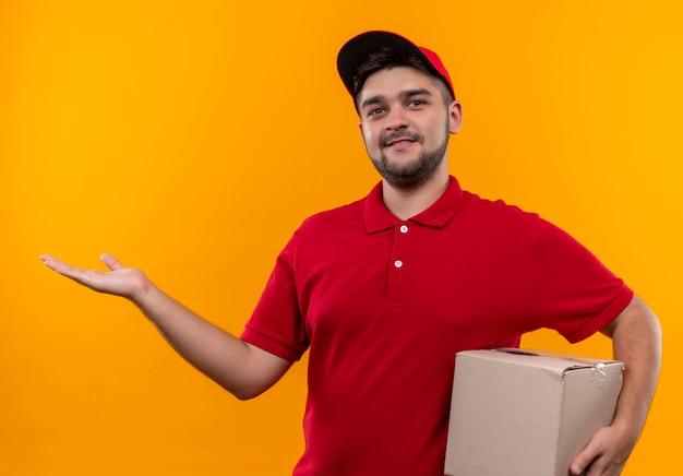 Jovem entregador de uniforme vermelho e boné segurando a embalagem da caixa, apresentando com o braço da mão copiar o espaço sorrindo