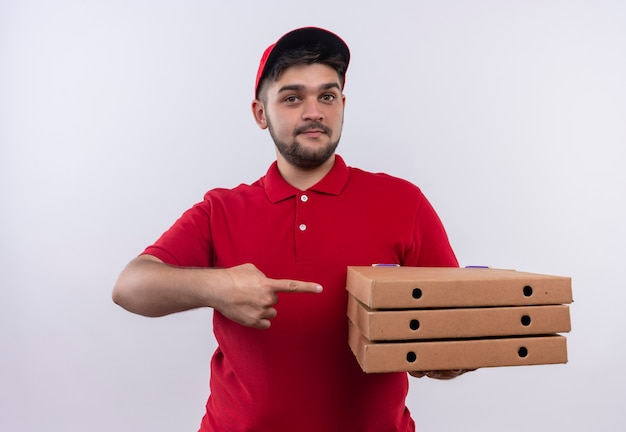 Jovem entregador de uniforme vermelho e boné segurando caixas de pizza apontando com o dedo indicador para elas e sorrindo amigável