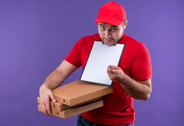 Jovem entregador de uniforme vermelho e boné segurando caixas de pizza e prancheta com páginas em branco sorrindo confuso e pedindo uma assinatura em pé sobre a parede roxa