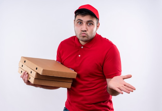 Jovem entregador de uniforme vermelho e boné segurando caixas de pizza, estendendo-se com o braço para o lado, parecendo confuso de pé sobre uma parede branca