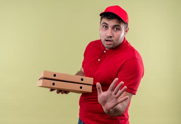 Jovem entregador de uniforme vermelho e boné segurando caixas de pizza fazendo sinal de pare com a mão e expressão de medo em pé sobre a parede verde