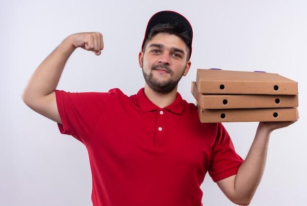 Jovem entregador de uniforme vermelho e boné segurando caixas de pizza levantando o punho e mostrando o bíceps, conceito vencedor
