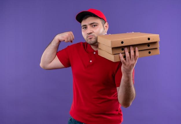 Jovem entregador de uniforme vermelho e boné segurando caixas de pizza, levantando o punho e parecendo confiante, o conceito vencedor em pé sobre a parede roxa