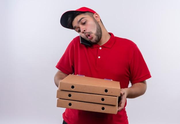 Jovem entregador de uniforme vermelho e boné segurando caixas de pizza muito ocupado falando no celular