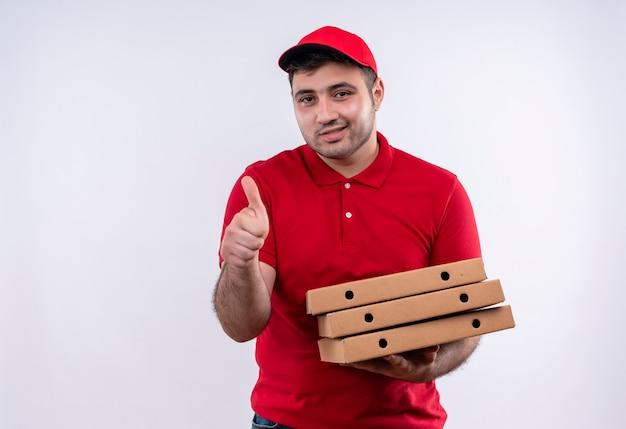 Jovem entregador de uniforme vermelho e boné segurando caixas de pizza, sorrindo alegremente e mostrando os polegares em pé sobre uma parede branca