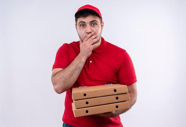 Jovem entregador de uniforme vermelho e boné segurando caixas de pizza sorrindo chocado cobrindo a boca com a mão em pé sobre uma parede branca