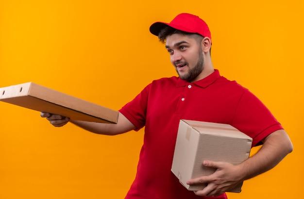 Jovem entregador de uniforme vermelho e boné segurando um pacote de caixa dando uma caixa de pizza para um cliente