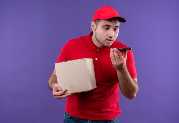 Jovem entregador de uniforme vermelho e boné segurando um pacote de caixa enviando mensagem de voz usando seu smartphone em pé sobre a parede roxa