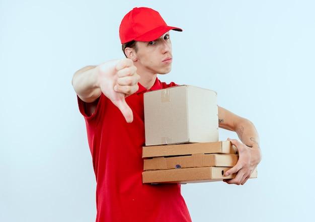 Jovem entregador de uniforme vermelho e boné segurando um pacote de caixas e caixas de pizza olhando para a frente descontente mostrando tumbas de pé sobre uma parede branca