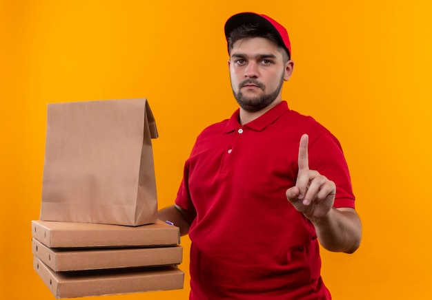 Jovem entregador de uniforme vermelho e boné segurando um pacote de papel e uma pilha de caixas de pizza mostrando um aviso no dedo indicador com uma cara séria
