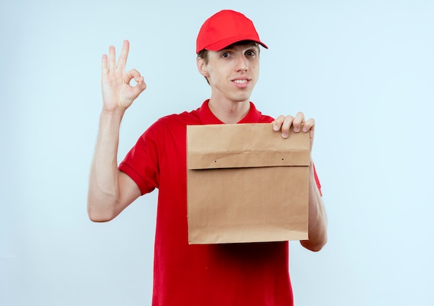 Jovem entregador de uniforme vermelho e boné segurando um pacote de papel, olhando para a frente com expressão confiante, mostrando a placa de ok em cima da parede branca