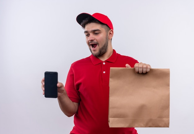 Jovem entregador de uniforme vermelho e boné segurando um pacote de papel sorrindo alegremente mostrando o smartphone