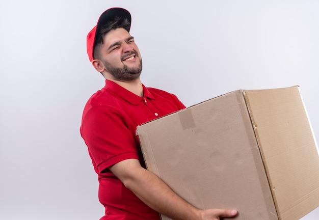 Jovem entregador de uniforme vermelho e boné segurando uma grande caixa de papelão sofrendo com o peso