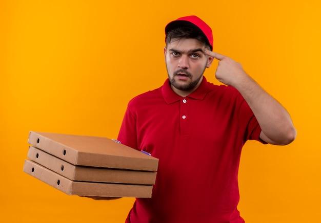 Jovem entregador de uniforme vermelho e boné segurando uma pilha de caixas de pizza apontando para a têmpora com uma cara séria e focada na tarefa
