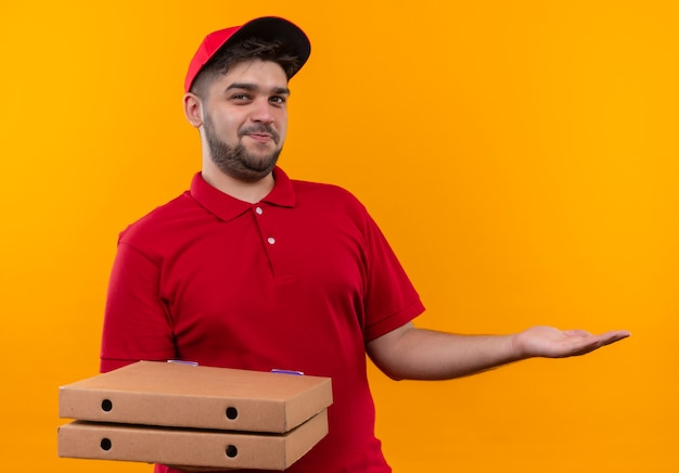 Jovem entregador de uniforme vermelho e boné segurando uma pilha de caixas de pizza, apresentando com o braço e a mão copiar o espaço