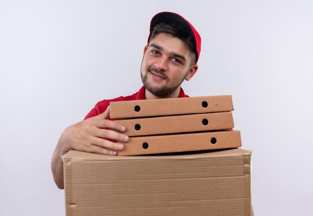 Jovem entregador de uniforme vermelho e boné segurando uma pilha de caixas de pizza e uma caixa de papelão, sorrindo amigável, olhando para a câmera