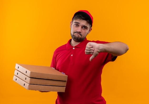 Jovem entregador de uniforme vermelho e boné segurando uma pilha de caixas de pizza mostrando o polegar para baixo com uma expressão triste no rosto